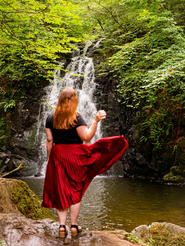 Woman in a red skirt standing in front of Glenoe Waterfall in Antrim Northern Ireland