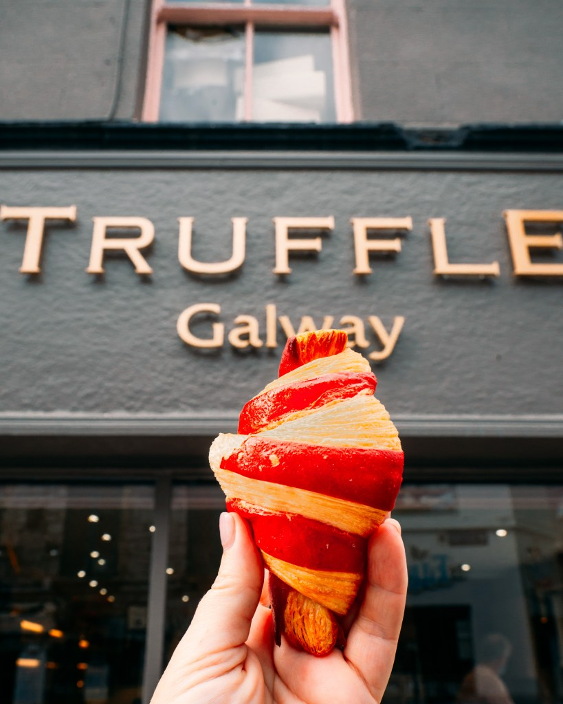 Woman holding up a pastry outside Truffle Galway on a Galway Food Tour