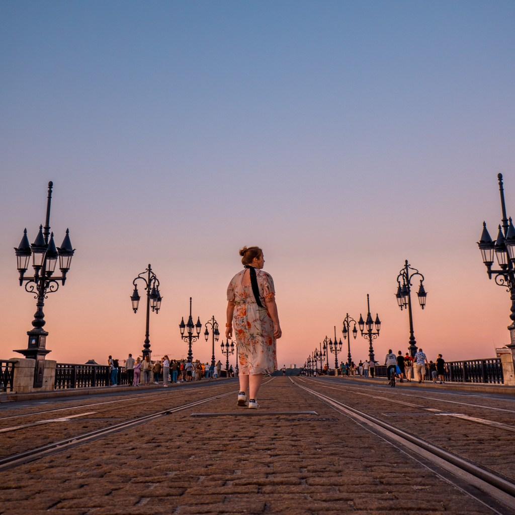 Woman in a floral dress crossing the Pointe de Pierre bridge in Bordeaux at sunset