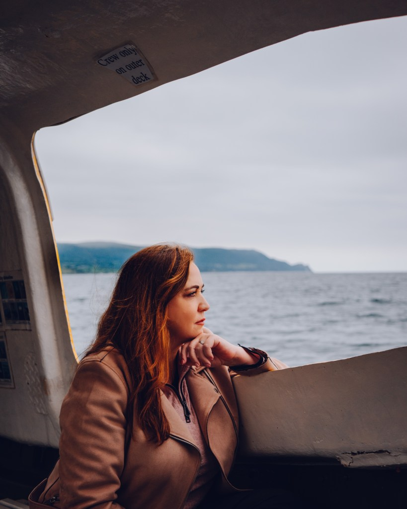 Woman sitting on a boat in Carnlough Harbour a hidden gem in Antrim