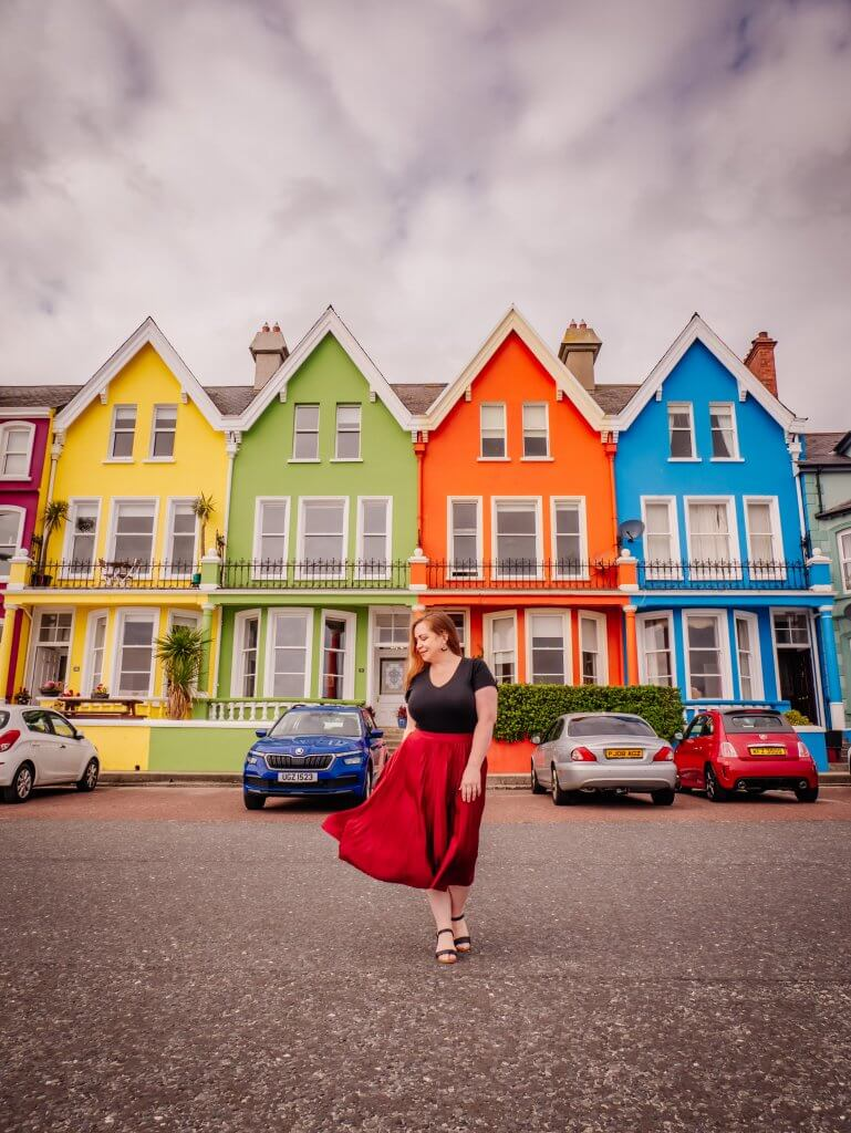 Woman standing in front of the colourful houses in Whitehead County Antrim