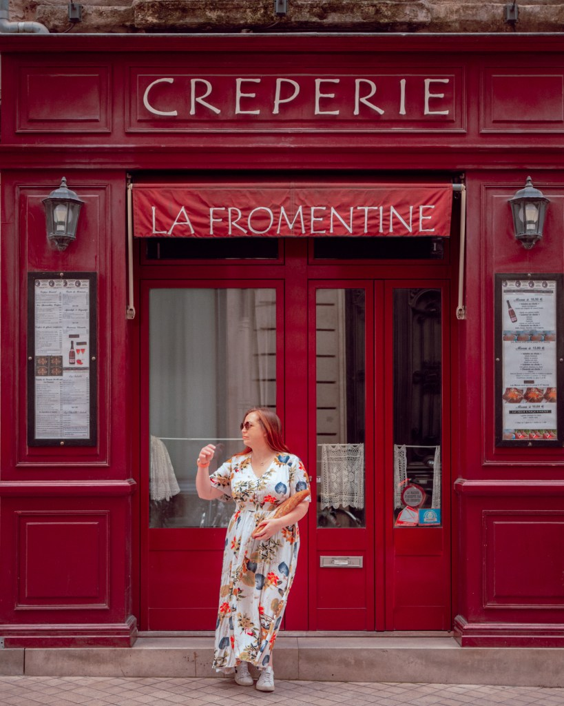 Woman standing outside la fromentine creperie in Bordeaux france with a baguette in her hand