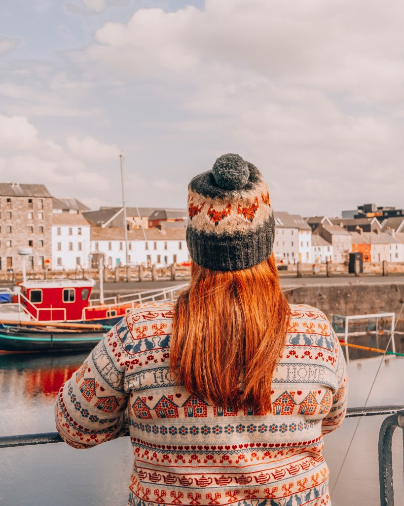 Woman wearing a woolly jumper and hat looking out over Galway Bay