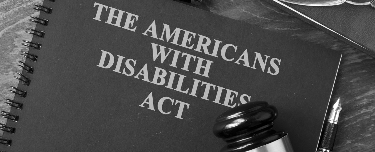 "A notebook titled ""The Americans with Disabilities Act"" with a gavel on top of the notebook and a pen next to it."