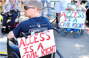 "Man in a wheelchair with a sign affixed to his wheelchair which reads ""access is a civil rights."""