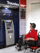 An image of a man sitting in a wheelchair looking at an ATM machine that is out of reach.