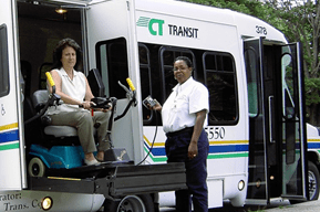 An image of a woman in a wheelchair exiting a paratransit bus.
