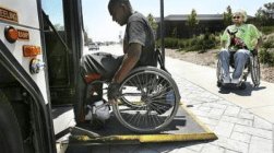 An image of a man in a wheelchair using a bus access ramp to board the bus.