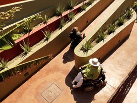 An image of two people in wheelchairs navigating to a building via an accessible ramp.