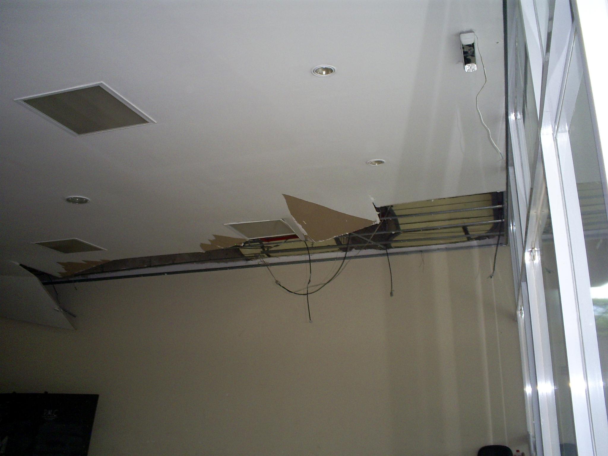 No saguão de entrada, o flagra. Um pedaço da cobertura do teto foi arrancado à mão, e a fiação elétrica cortada.
