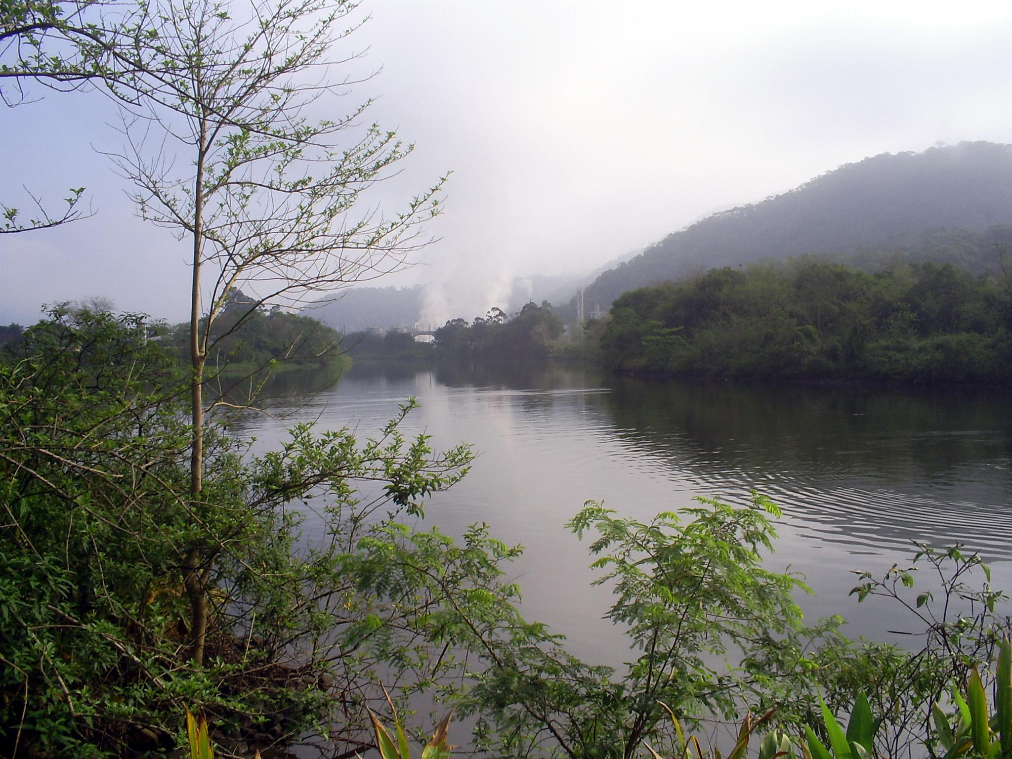 Rio Cubatão. Ao fundo, as incessantes chaminés das indústrias. Foto: Allan Nóbrega