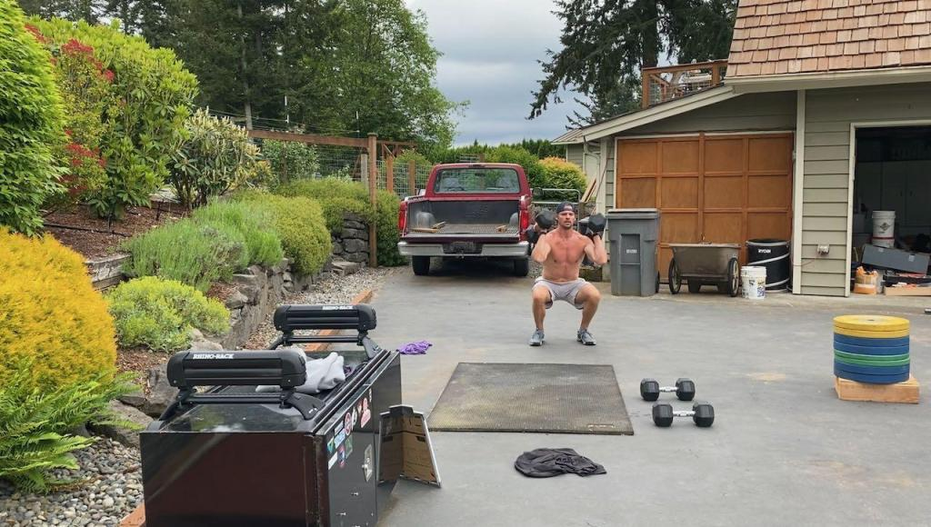 Joe doing dumbbell thrusters in the driveway