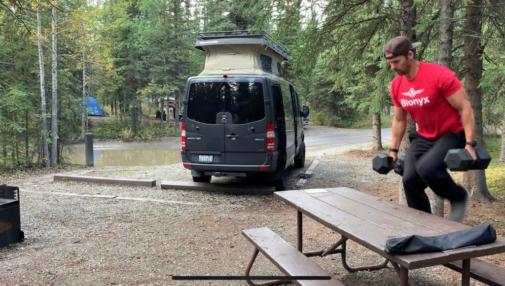 Joe doing some dumbbell fitness in a campground.