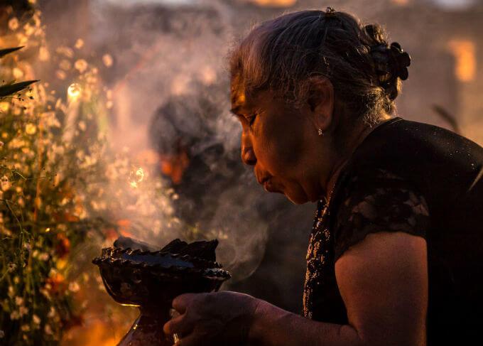 墓に祈りを捧げる女性