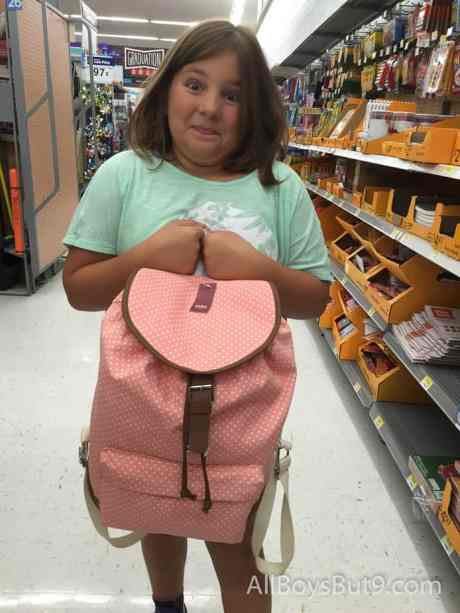 Gracie holding a backpack to fill for school!