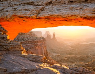 Mesa Arch glows from reflected light at sunrise in Canyonlands National Park, UT