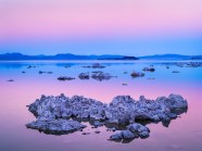 Layers of pink and blue light at dusk highlight tufa formations in Mono Lake