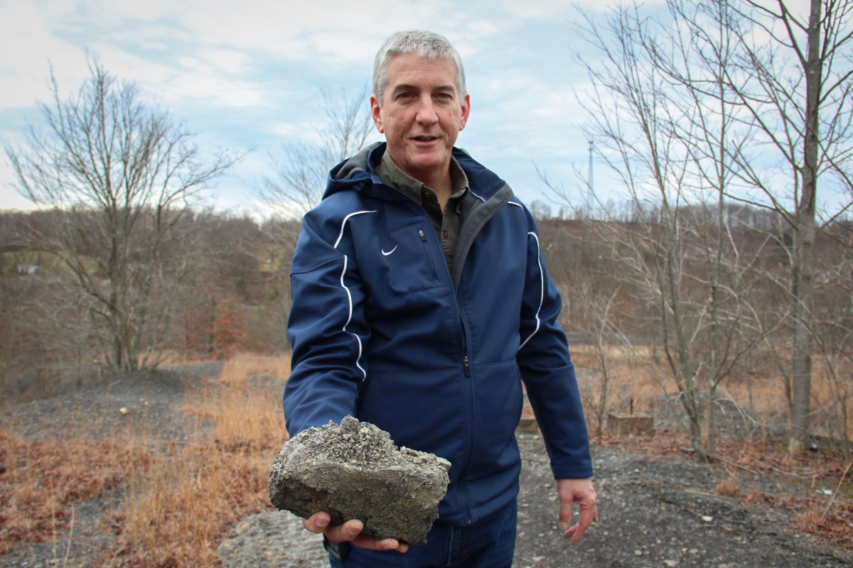 Eric Cavazza, director of Pennsylvania's Bureau of Abandoned Mine Reclamation, holds up some coal refuse from the waste pile in Fredericktown. The white powder on the rock easily dissolves during rain storms, and the acidic runoff damages rivers and streams. Photo: Reid Frazier