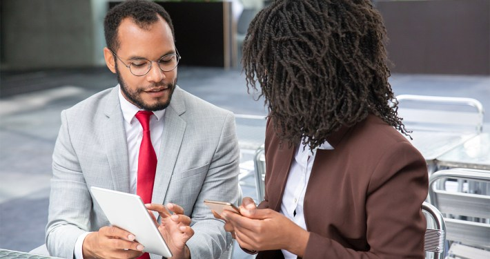 African American business man and woman looking at digital tablet
