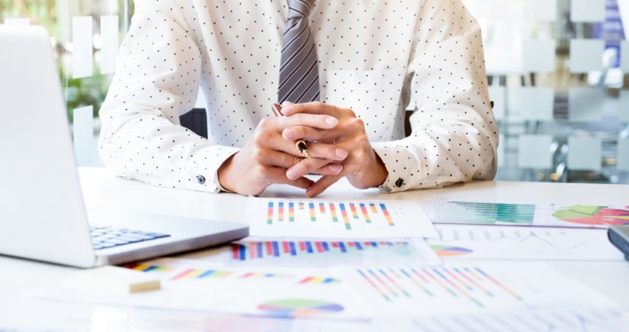 Image of business man in a tie and shirt analyzing business analytics