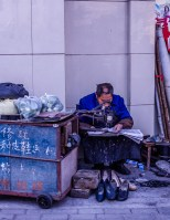 Day Three: this cobbler reads the newspaper while he waits for customers. His sidewalk shop is down the block from our apartment, on the corner of Weifeng Xi Lu and Pudong Lu.