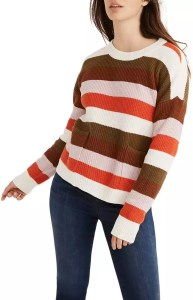 A woman wearing a striped patch pocket pullover sweater.