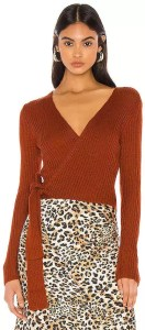 A woman wearing a burnt orange wrap sweater with a leopard print skirt.