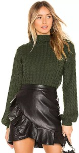 A woman wearing a dark green knit sweater tucked into a leather skirt.