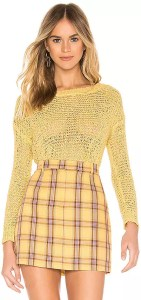 A woman wearing a yellow knit sweater tucked into a yellow plaid skirt.