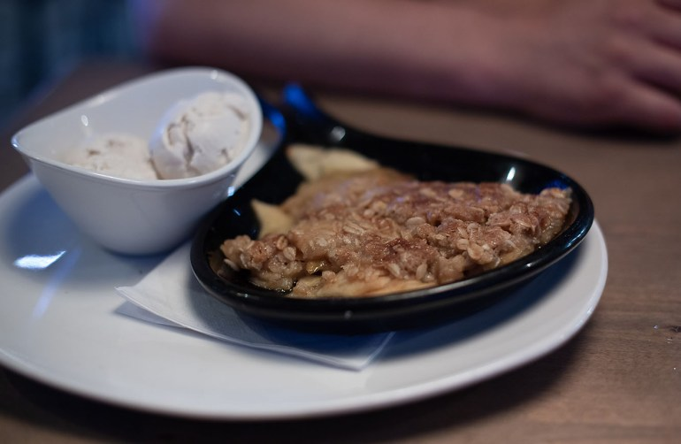 Baked apple crisp in skillet with coconut ice cream