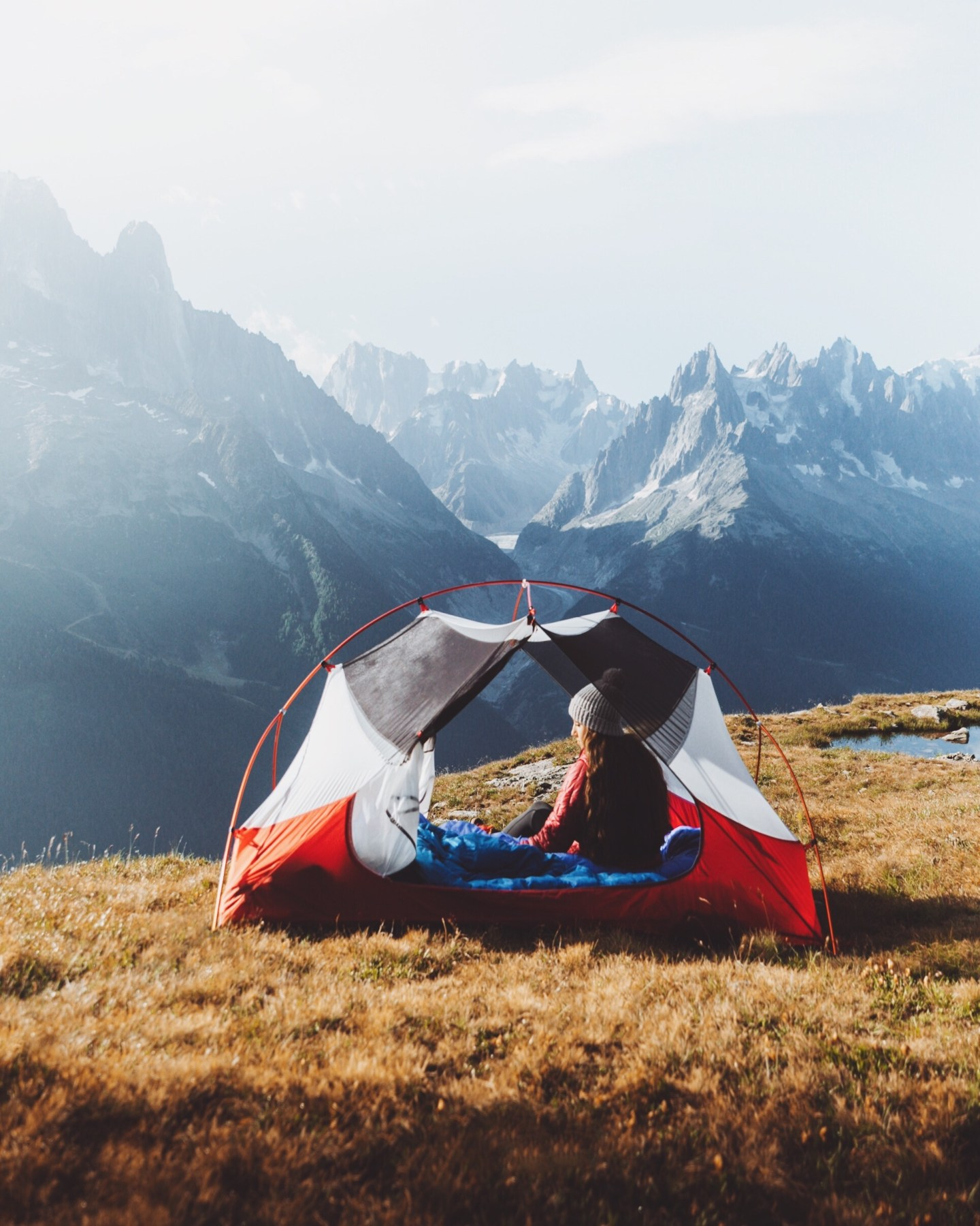 Girl camping in a tent with a view of tall, pointy mountains