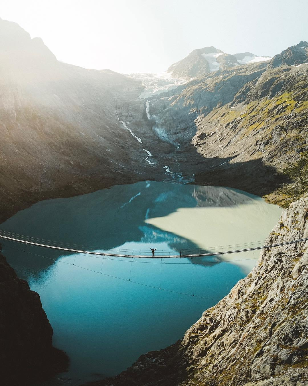 Triftbrucke Suspension bridge at sunrise with a man standing on the suspension bridge over the turquoise lake