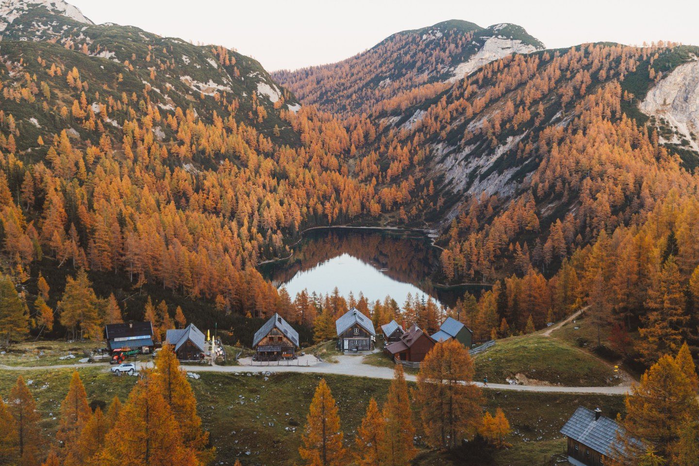 Steirersee surrounded by fall larches and cabins