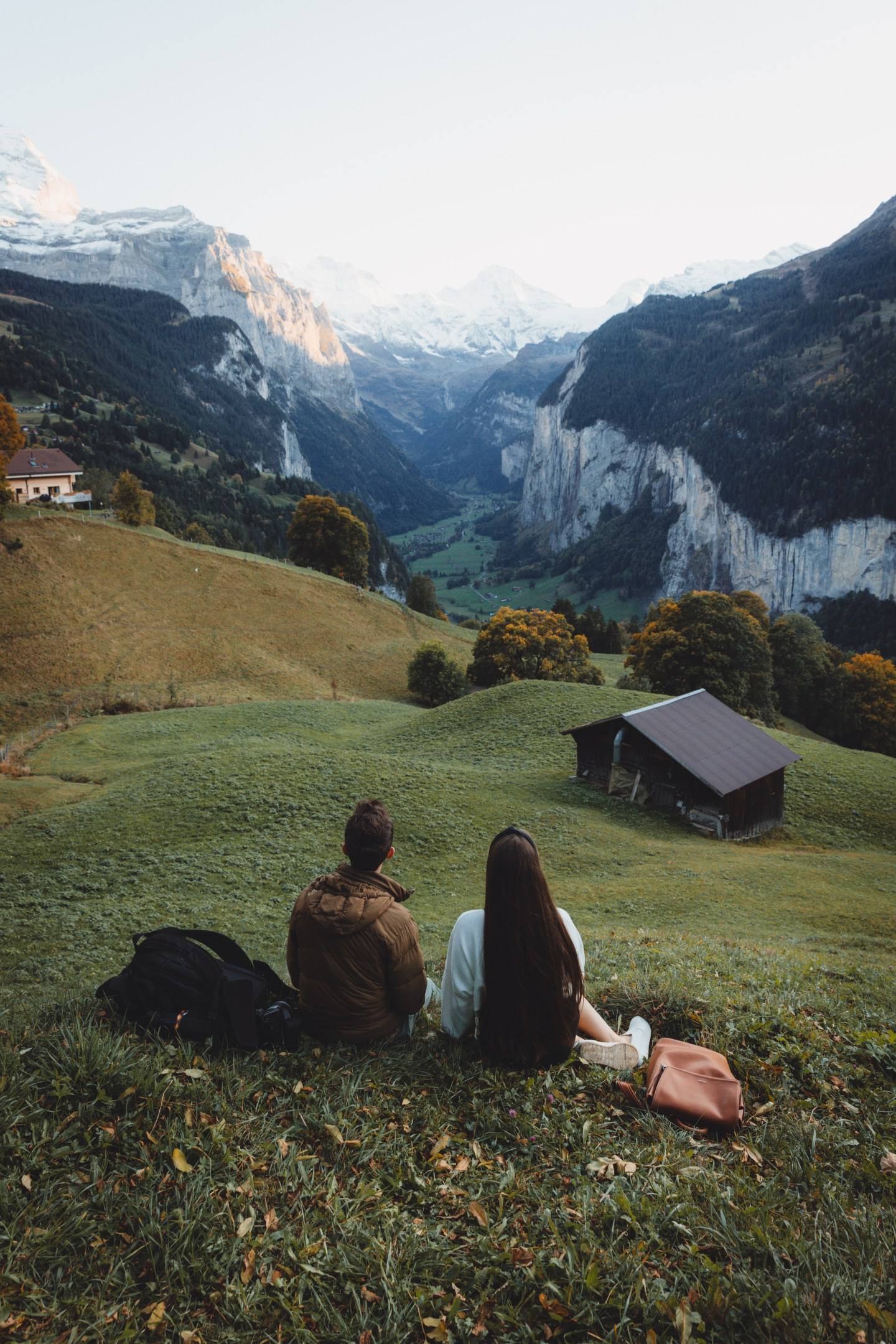 Two friends sitting in a field in Wengen, Switzerland