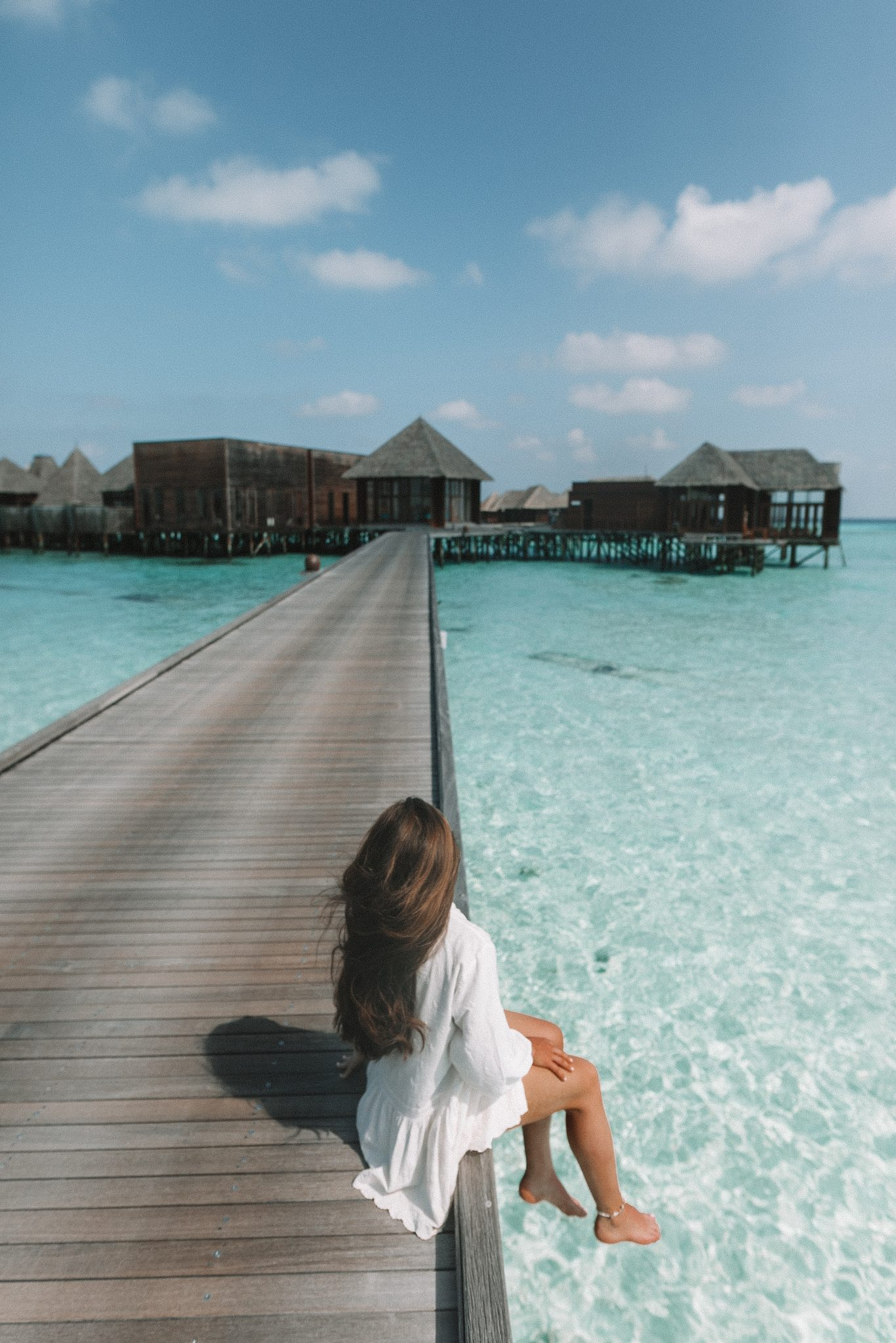 Girl sitting on the edge of a boardwalk in the Maldives
