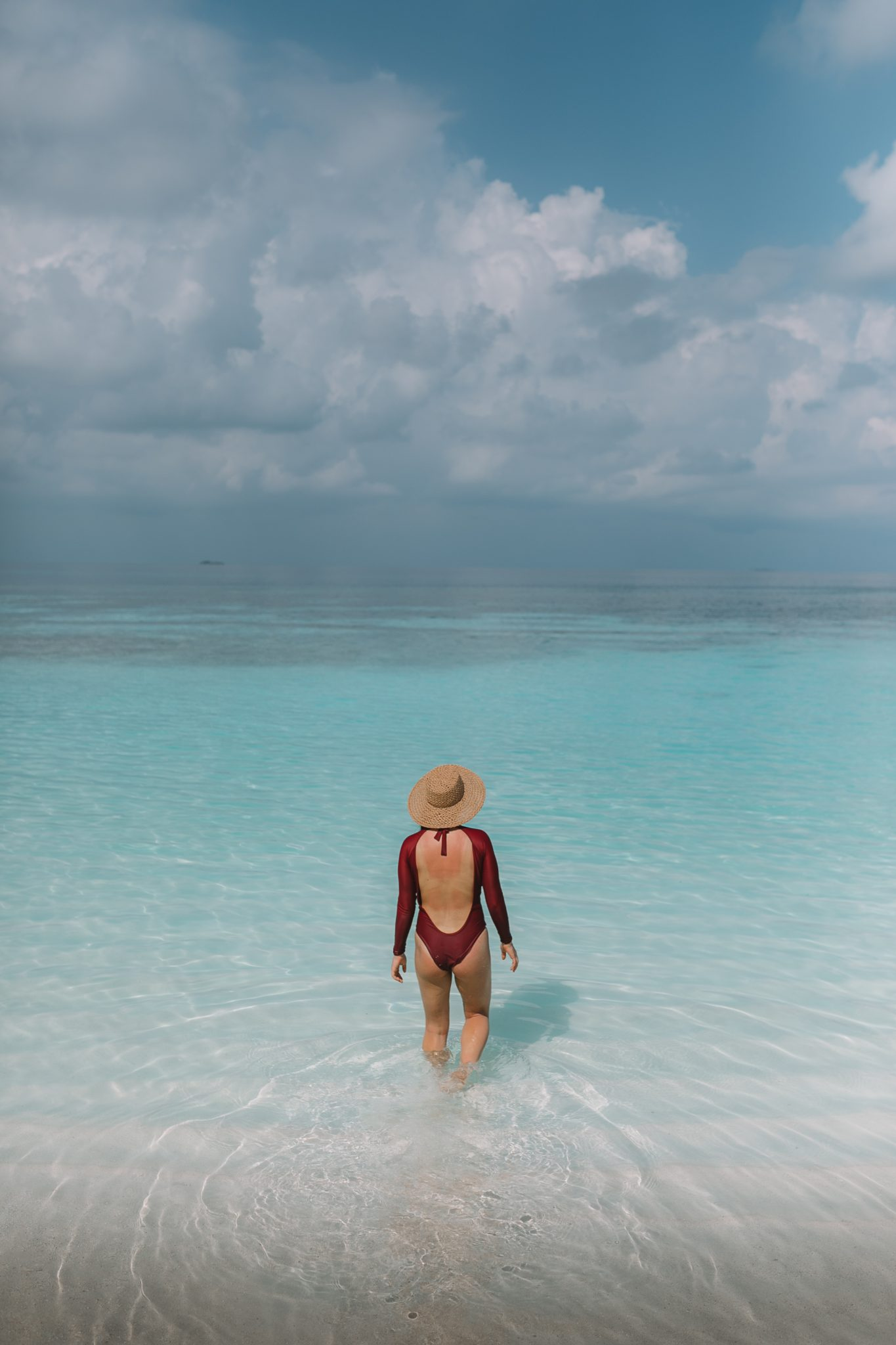 Girl walking into the ocean in the Maldives