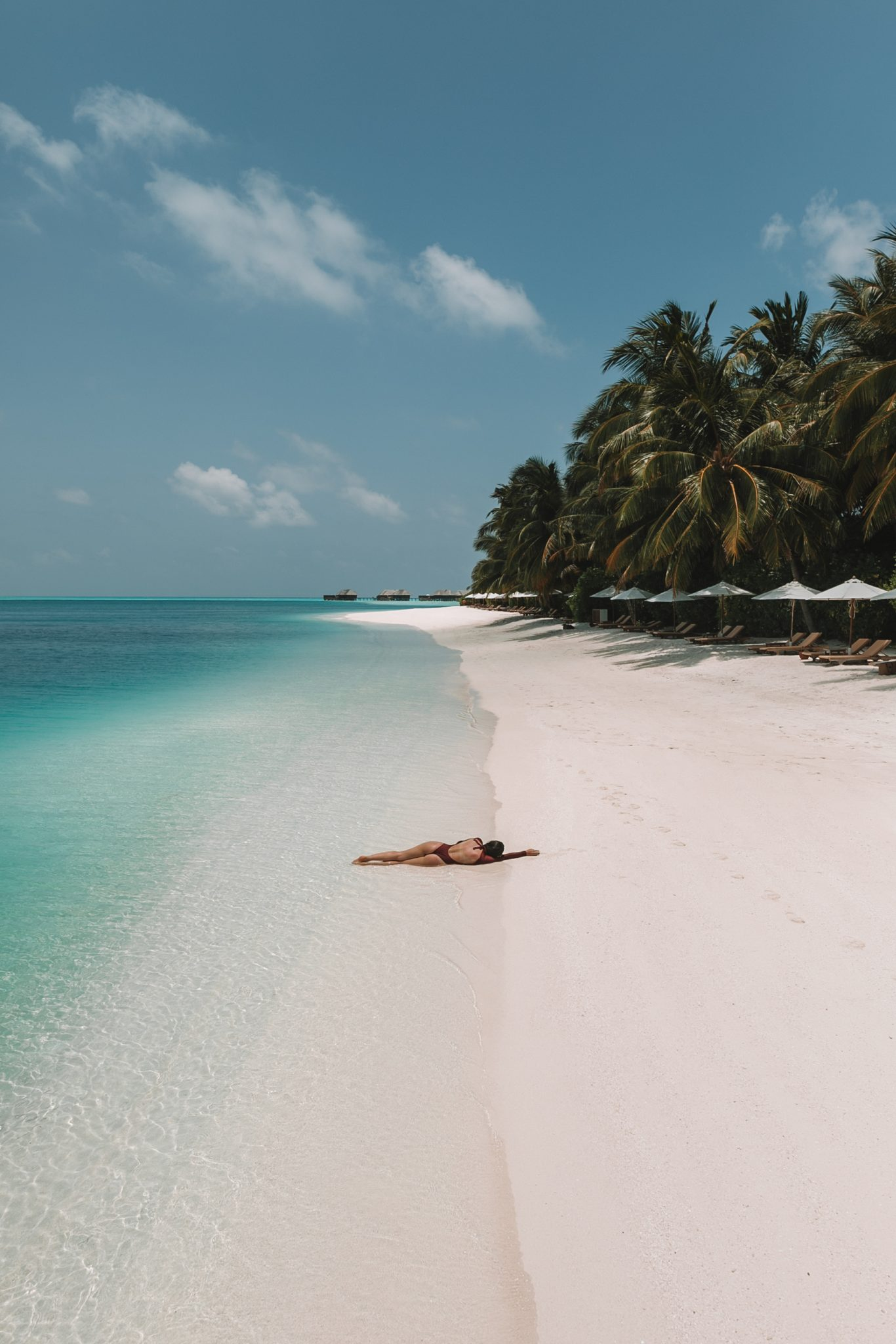 Girl laying on a whitesand beach in the Maldives