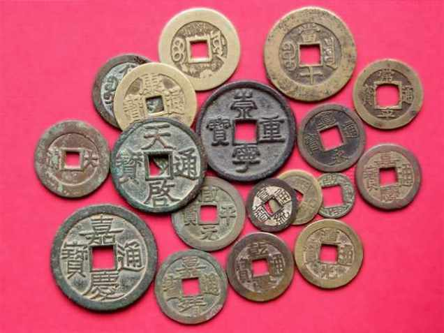 Ancient Chinese coins with Chinese writing on them and squares cut out in the middle.