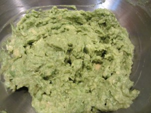 Avocados and spices mashed with potato masher.