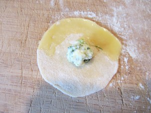Filling placed in the center of the dough, and one edge brushed with egg wash.