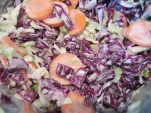 The cabbage, along with a sliced carrot, added to the dressing.