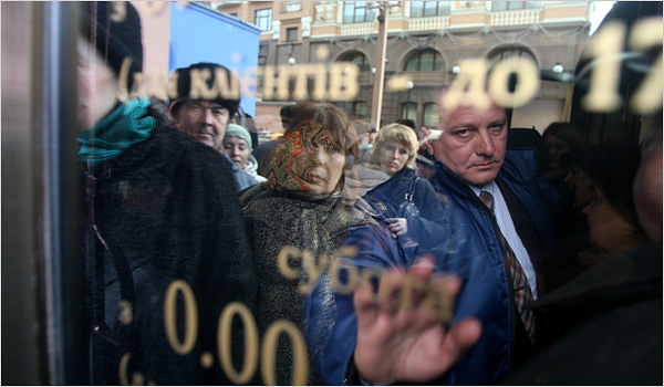 Dozens waited outside the Rodovid Bank in Kiev on Friday to take money out of their accounts. The bank is close to failing. (Joseph Sywenkyj, NYT)