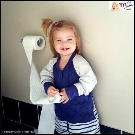 Toddler wearing The Sleepy Company X-TEND Sleepsuit while pulling toilet paper off the roll