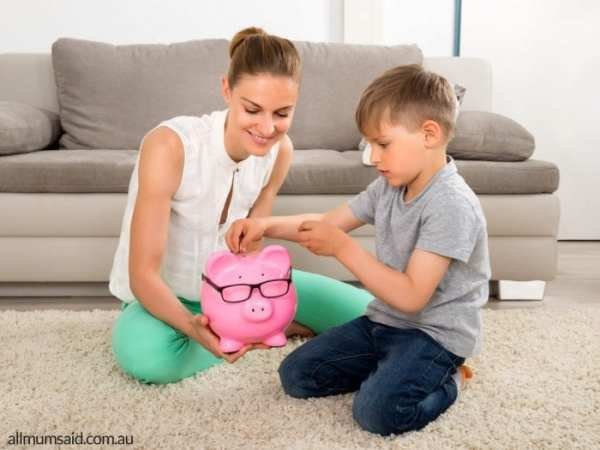Ways to tech kids to save   mum and son putting money into piggy bank