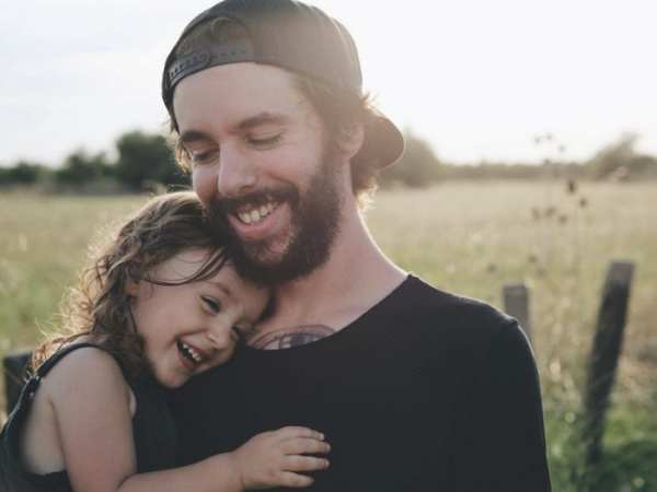 young girl hugging dad and laughing