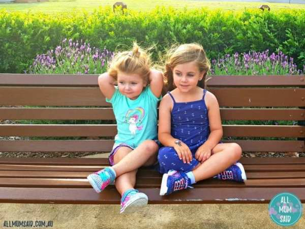 sisters sitting on park bench wearing kids Skechers shoes