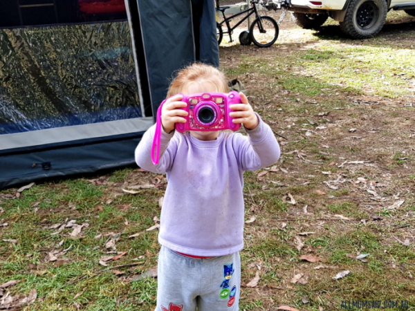 girl using Vtech Kidizoom camera camping