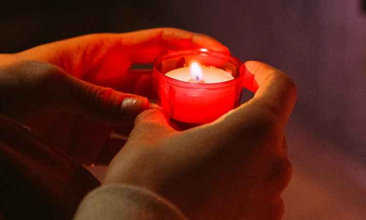 person holding red candle in a dark room