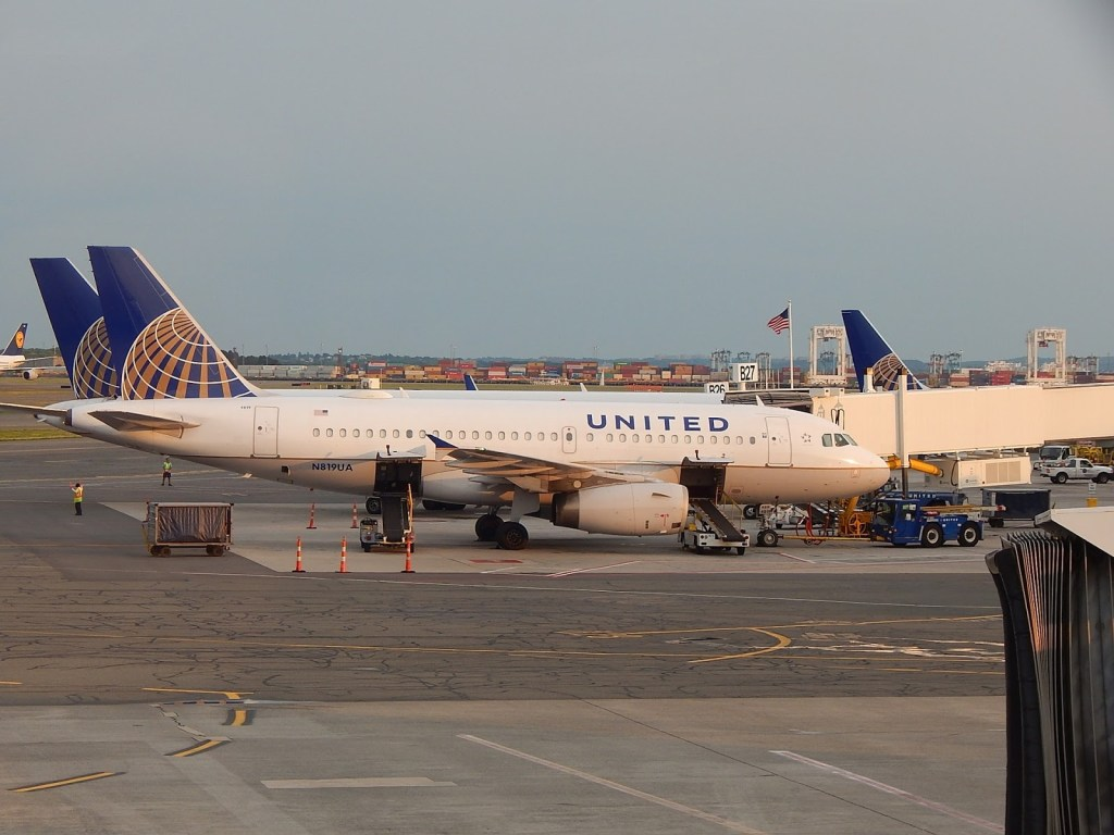 United Airlines jet docked at gate.