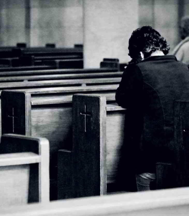 unrecognizable men praying in old catholic church